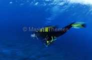 Diver descending in channel with strong current. (This image contains deliberate blurring.)
