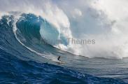 Surfer riding large wave.