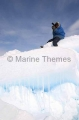 Inuit hunter scanning sea ice for seals from high vantage point created by pressure from wind and tides.