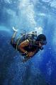 Scuber diver descending among scuba bubbles.