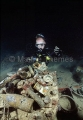 Diver at night with artifacts on the deck of the Shinkoku Maru, Japanese WW II shipwreck.